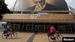 Адамдар велосипедпен 67-Канн кинофестивалінің ресми плакаты жанынан өтіп барады. 12 мамыр 2014 жыл.