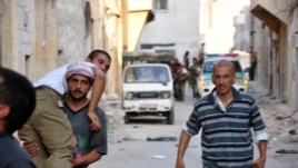 Syria - Syrian rebels assist a comrade during clashes with government troops in the Salhin district of the northern city of Aleppo, 31Jul2012