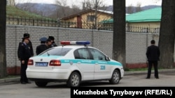Полицейские и люди в гражданском у здания посольства Узбекистана в Алматы. 29 марта 2015 года.