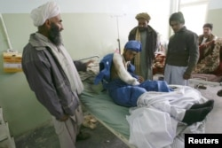 An Afghan man receives treatment in a Herat hospital after he was wounded in a suicide bombing in Farah Province in April.