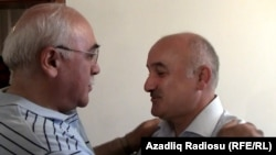 Musavat party deputy leader Arif Hajili (right) is greeted by an acquaintance in Baku after his release from prison on June 22.