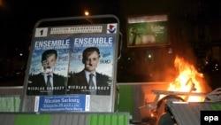 Несогласная Франция отметила победу правых (Саркози на рекламном плакате с пририсованными усиками) ночными погромами