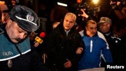 Полиция Румынияның бұрынғы премьер-министрі Адриан Нэстасені (ортада) түрмеге апара жатыр. Бухарест, 6 қаңтар 2014 жыл.