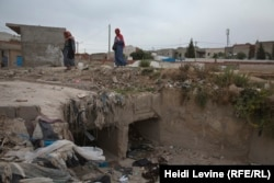 Tunisian women cross over a trench full of garbage in the poverty-stricken town of Douar Hicher, northeast of Tunis.