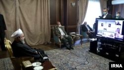 President Hassan Rouhani holding a teleconference with top aides as a coronavirus preventive measure, while many people are in the room. March 15, 2020