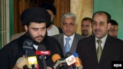 Iraqi Prime Minister Nuri Kamil al-Maliki (right) looks on as Muqtada al-Sadr speaks to the media (file photo)