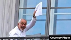 Iranian Foreign Minister Mohammad Javad Zarif waves to reporters from his hotel balcony during the nuclear talks in Vienna on July 13.