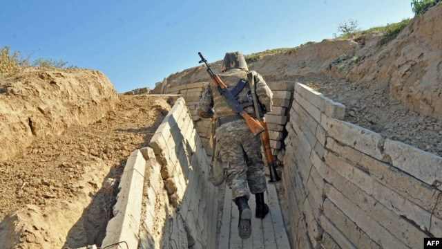 An Armenian soldier runs in trenches on the border of the disputed of Nagorno-Karabagh region.