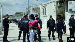 Грекияның Лесбос аралындағы лагер жанында жүрген мигранттар мен полицейлер. 16 наурыз 2017 жыл.