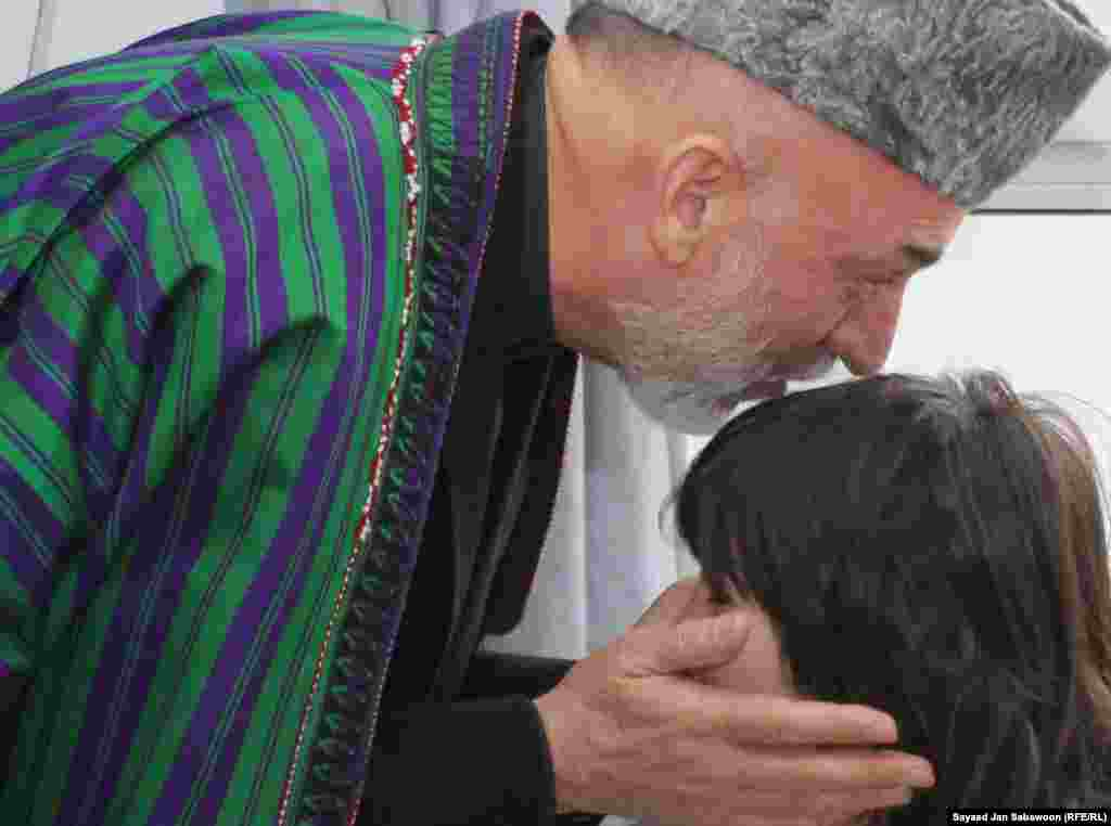 Afghanistan -- President Hamid Karzai kisses the head of a girl who was wounded in prevoius day's suicide bomb attack during an Ashura mourning procession, as he visits victims at the Emergency Hospital in Kabul, 07Dec2011