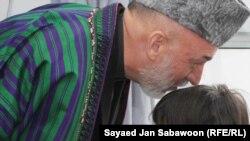 دافغانستان ولسمشر حامد کرزی د یوې ماشومې انجلۍ سر ښکلوي چې د ګل ورځ په کابل کې د عاشورې په مراسمو کې په ځانمرګي برید کې ژوبله شوېده.۷ ډسمبر ۲۰۱۱