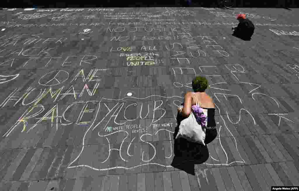 "A protester writes with chalk during a ""Black Trans Lives Matter"" march against police brutality on June 17, 2020 in the Brooklyn Borough of New York City."