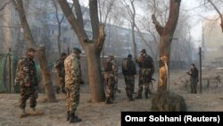 Afghan security forces inspect the site of a suicide attack in Kabul on January 5.
