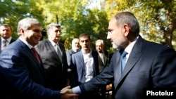 Armenia -- Prime Minister Nikol Pashinian (R) greets Aram Sarkisian at a memorial to the victims of the October 1999 deadly attack on the Armenian parliament, Yerevan, October 27, 2019.