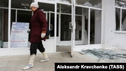 A woman walks past a school building damaged by recent shelling in the city of Donetsk in November.