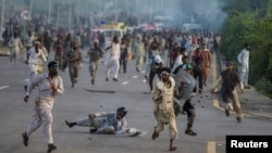 Antigovernment protesters run after police personnel during the Revolution March in Islamabad on September 1.