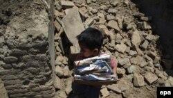 Petogodišnji dečak Arus skuplja svoje knjige iz kuće nakon zemljotresa