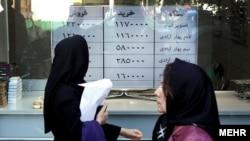 People walk in front of currency exchanges in Tehran.