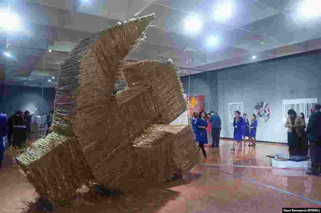 """Художник Асхат Ахмедияров для выставки соорудил серп и молот из камыша. """"Я смотрю на город через железный занавес того времени. Я бы хотел в себе искоренить этот сорняк. Камыш по большей части - это сорняк, который распространяется корнями. Трудно от него избавиться. Я бы хотел, чтобы в современной Астане не было этого сорняка,"""" - делится Асхат Ахмедияров."""