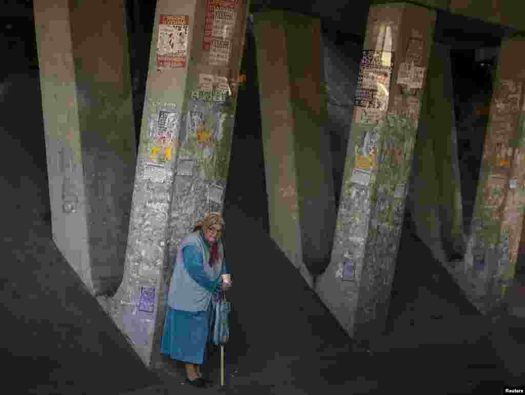 An elderly woman begs under a highway bridge in Kyiv, Ukraine. (Reuters/Gleb Garanich)