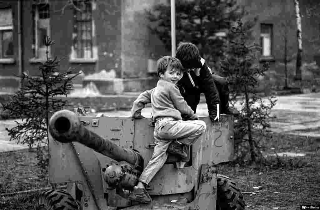 Djeca izbjeglice iz Bosne i Hercegovine u izbjegličkom kampu u Varaždinu, Hrvatska, u zimu 1992. godine. Dječak lijevo je Elvis, na fotografiji u igri sa prijateljem oko topa.