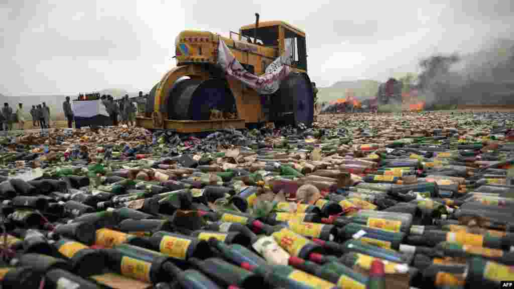 An official uses a steamroller to crush bottles of alcohol during a ceremony to mark International Day Against Drug Abuse and Illicit Trafficking in Karachi, Pakistan. (AFP/Asif Hassan)