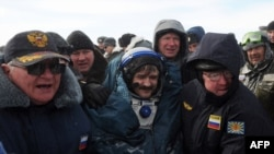 Ailing? Russian space agency rescuers help cosmonaut Aleksandr Kaleri shortly after his landing near the town of Arkalyk, in Kazakhstan on March 16.