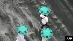 Hajj pilgrims seek cover as heavy rain streams down a road in Mecca on November 25.