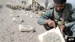 An Afghan policeman points to a mark on a landmine found in Ghurian district in Herat Province (file photo)