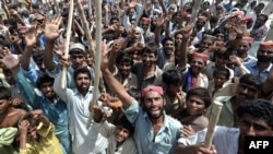 Internally displaced men block a road as they protest against the shortage of relief aid and the Pakistani government's handling of the crisis in Sukkur in September.