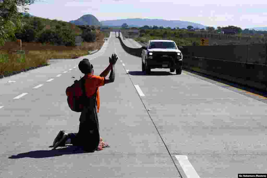 A migrant, part of a caravan of thousands traveling from Central America en route to the United States, attempts to hitchhike on a motorway on the outskirts of Guadalajara, Mexico. (Reuters/Go Nakamura)