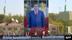 Участники демонстрации в Душанбе стоят на фоне гигантского портрета президента Таджикистана Эмомали Рахмона.