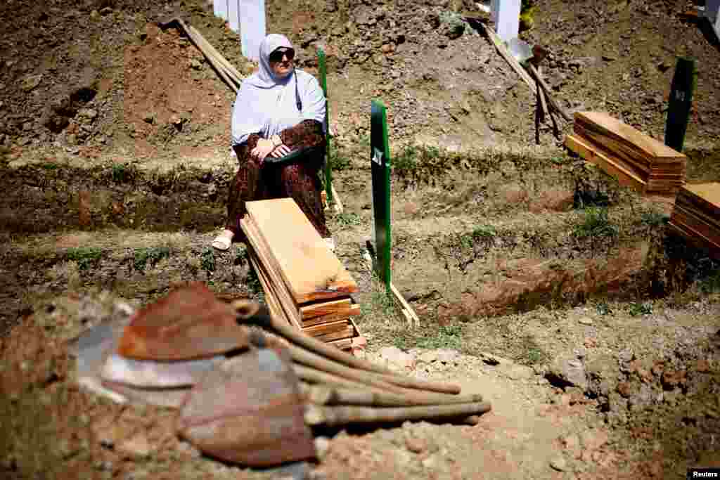 A Bosnian Muslim woman sits near a grave before a mass funeral in the Memorial Center in Potocari, near Srebrenica. (Reuters/Dado Ruvic)