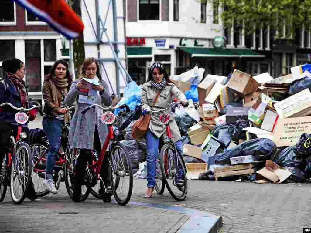Турысты – на заваленых сьмецьцем вуліцах Амстэрдаму. Тамтэйшыя сьмецяры страйкуюць з 6 траўня, дамагаючыся падвышэньня заробкаў і лепшых умоваў працы.