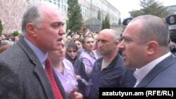 Armenia -- Gloria factory owner Bagrat Darbinian (L) argues with a police officer, Vanadzor, April 21, 2020.