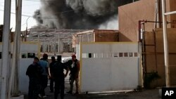 Iraqi security forces secure the site of a fire that broke out at Baghdad's largest ballot-box storage site, where ballots from Iraq's May parliamentary elections were stored, in Baghdad on June 10.