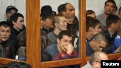 Defendants in Zhanaozen riots case look out of a glass cubicle during a court session in the Caspian port city of Aqtau on March 27.