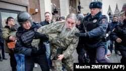 Russian riot police detain an opposition activist during a protest rally in central Moscow on November 5.