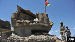 Afghan border policemen walk past a bunker, destroyed during recent clashes between Afghan border police and Pakistani troops in Goshta district of Nangarhar Province.