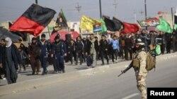 صورة من الأرشيف لجندي عراقي يحرس موكباً لزوار في طريقهم إلى كربلاء