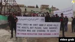Pamje nga një demonstratë e banorëve në Madaja në Siri ku ata kërkojnë ndihmë