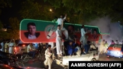 Supporters of Pakistan's cricketer-turned politician Imran Khan, head of the Pakistan Tehreek-e-Insaf (Movement for Justice) party, celebrate on a street during general election in Islamabad on July 25, 2018.