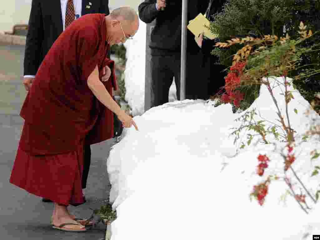 The Dalai Lama touches snow at the White House following a meeting with U.S. President Barack Obama. - Photo by Michael Reynolds for epa