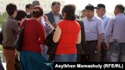 """Люди окружили главного редактора газеты """"Жас Алаш"""" Рысбека Сарсенбая возле суда, где проходит суд по событиям в Шетпе. Актау, 10 мая 2012 года."""