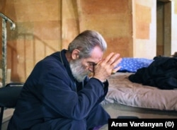 Archbishop Pargev Martirosian, the current primate of the Artsakh Diocese of the Armenian Apostolic Church, prays as artillery fire is heard landing in Stepanakert.