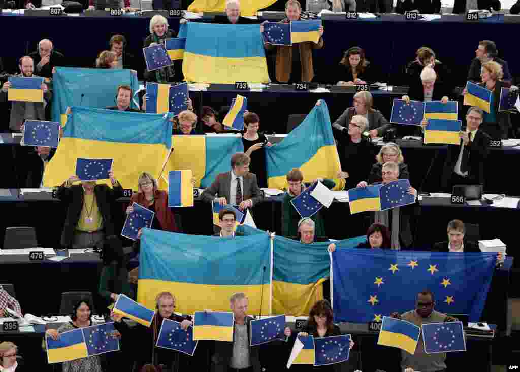 Members holding EU and Ukrainian flags vote in the European Parliament in Strasbourg. (AFP/Frederick Florin)