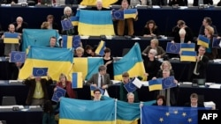 Membri ai Parlamentului European protestînd cu steagul Ucrainei...