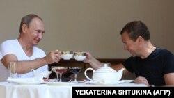 Президентът на Русия Владимир Путин и премиерът Дмитрий Медведев закусват по време на отпуск в резиденцията в Сочи. Снимката е от 2015 г.