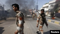 Pakistan -- Rangers disperse angry protesters who set ablaze tires after a rocket hit a wall of a religious school in Karachi , 23Mar2011