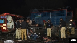 Pakistani policemen and volunteers move the bodies of victims at the site of a bomb explosion in Lahore on February 13.